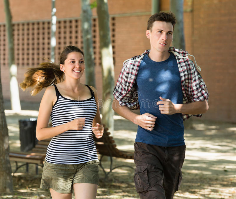 Uśmiechnięci młodzi ludzie biegać plenerowy zdjęcie stock