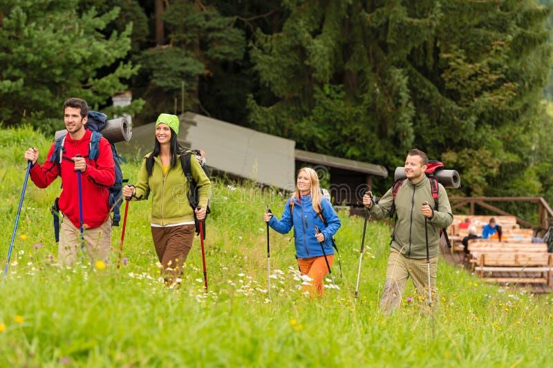 Uśmiechnięci młodzi przyjaciele wycieczkuje na wzgórzu fotografia stock
