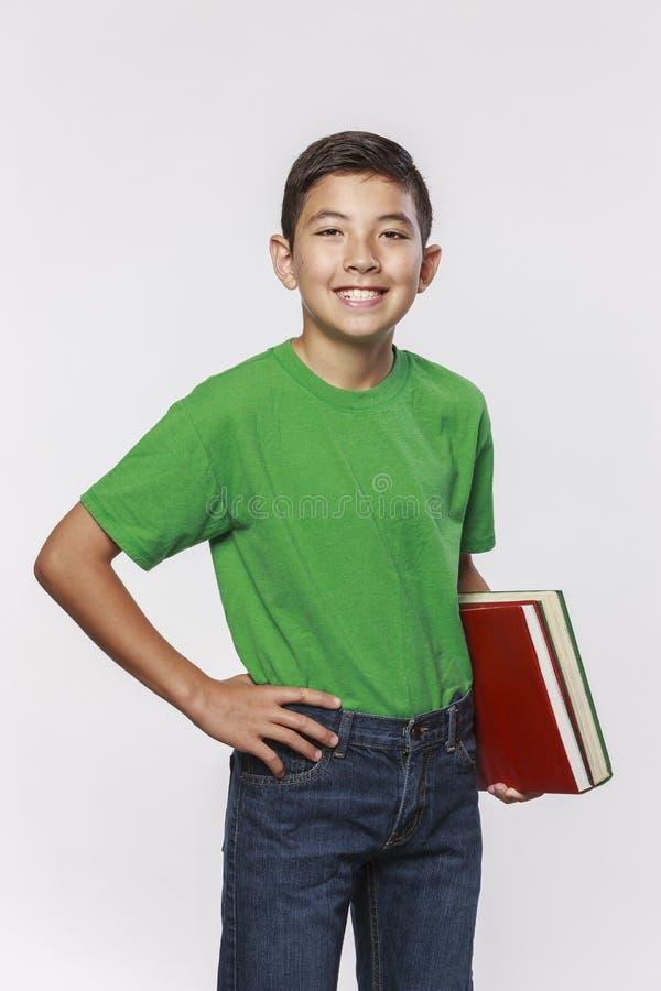 Uśmiechnięci młodzi męskiego ucznia mienia podręczniki zdjęcie royalty free