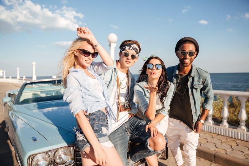 Uśmiechnięci młodzi przyjaciele stoi outdoors w lecie wpólnie obraz stock
