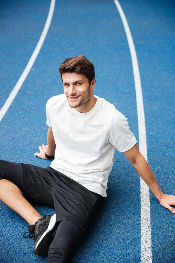 Uśmiechnięci młodzi sporty obsługują obsiadanie przy stadium obraz stock