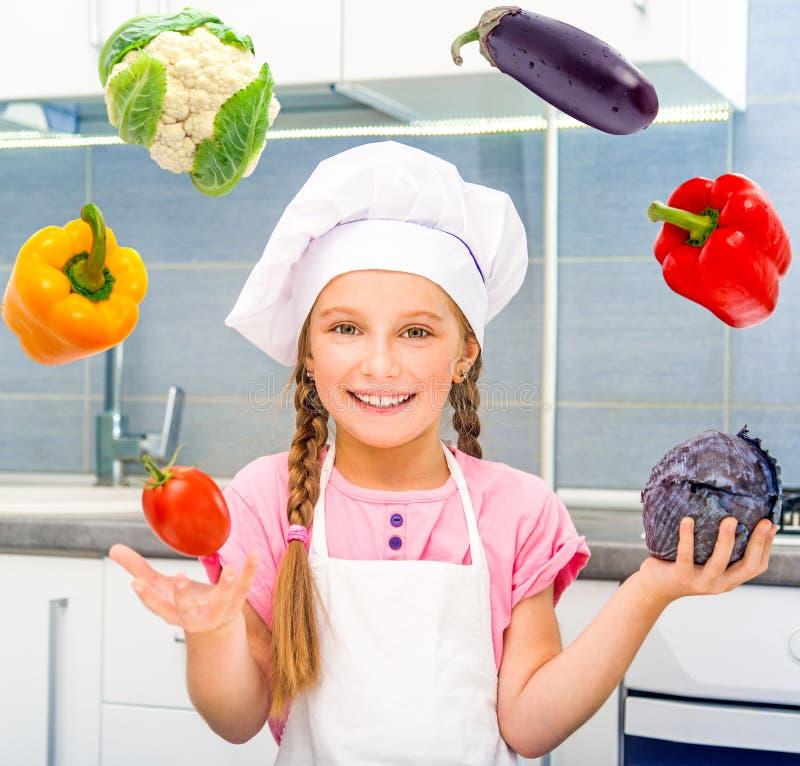 Uśmiechnięci małej dziewczynki żonglerki warzywa zdjęcia stock