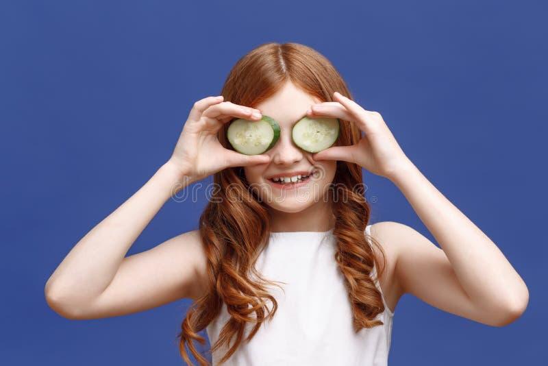 Uśmiechnięci małej dziewczynki mienia plasterki ogórek obraz royalty free
