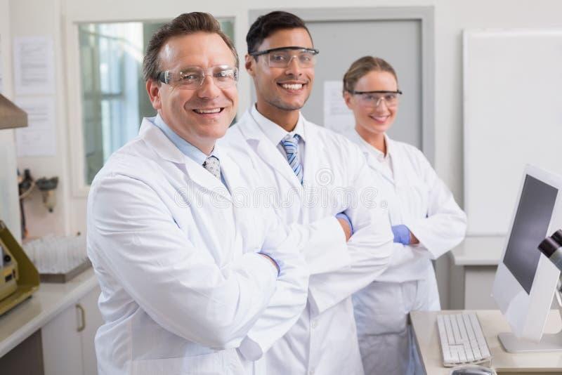 Uśmiechnięci naukowowie patrzeje kamer ręki krzyżować obraz stock