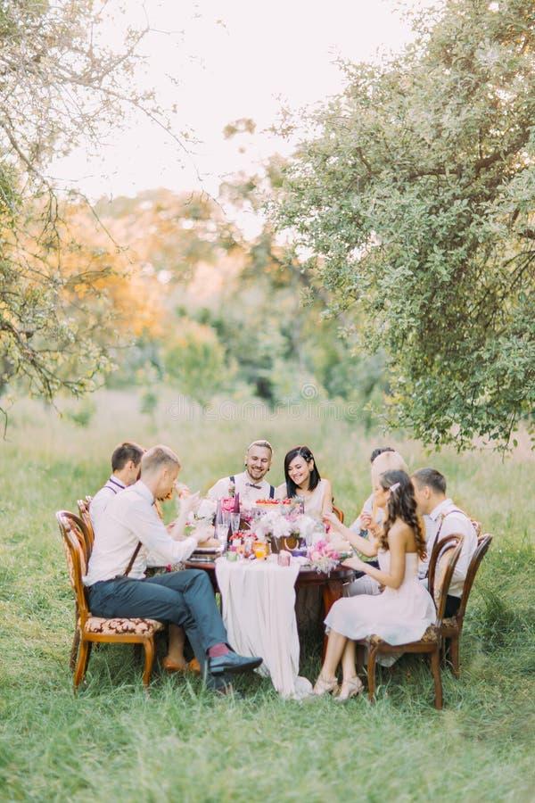 Uśmiechnięci nowożeńcy i goście świętują szczęśliwego wydarzenie w pogodnym parku ślubny gość restauracji obraz royalty free