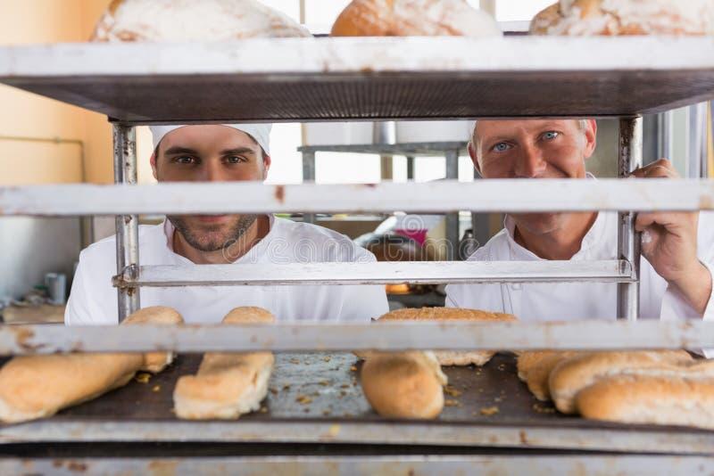 Uśmiechnięci piekarzi patrzeje przez tacy chleb obrazy stock