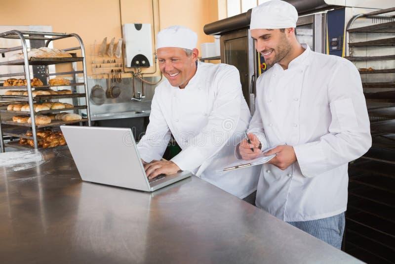 Uśmiechnięci piekarzi pracuje wpólnie na laptopie zdjęcie stock