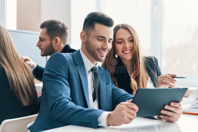Uśmiechnięci pomyślni ludzie biznesu dyskutuje pomysły używać cyfrową pastylkę w biurze zdjęcia royalty free