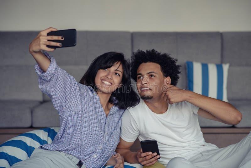 Uśmiechnięci potomstwa dobierają się brać selfies w łóżku używać smartphone, są łgarskim puszkiem i pozować zdjęcia stock