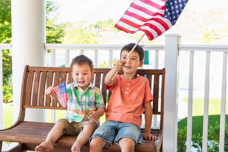 Uśmiechnięci potomstwa Mieszający Biegowi Chińscy Kaukascy bracia Bawić się Z flaga amerykańskimi zdjęcia royalty free