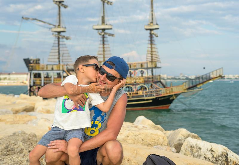 Uśmiechnięci potomstwa ojcują buziaka syna blisko morza na zmierzchu szczęśliwy dzień lato Pojęcie życzliwa rodzina zdjęcia royalty free