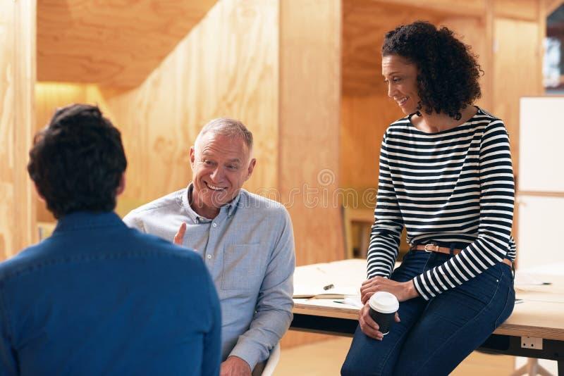 Uśmiechnięci praca koledzy opowiada wpólnie w biurze zdjęcie stock