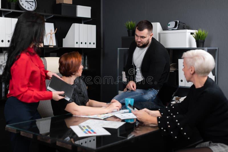 Uśmiechnięci pracownicy opowiada w miejsce pracy fotografia stock