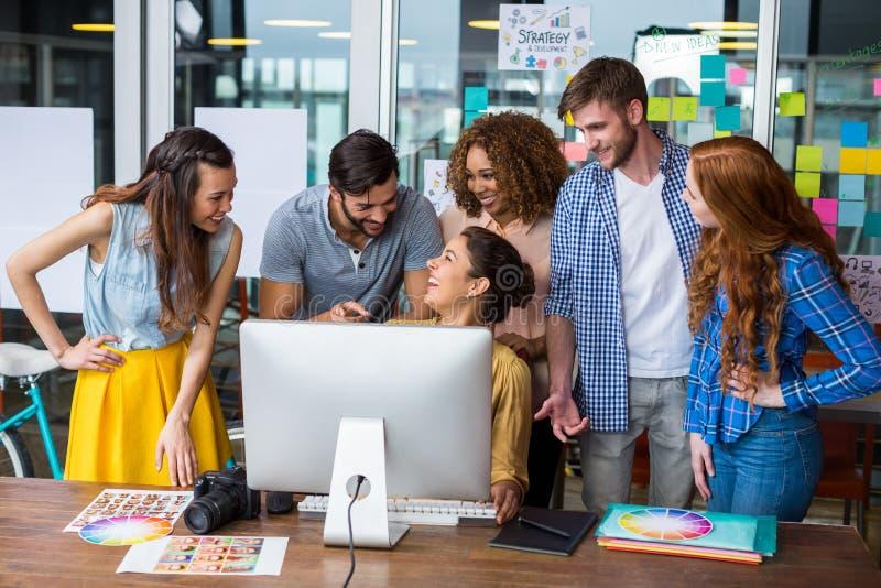 Uśmiechnięci projektant grafik komputerowych oddziała wzajemnie z each inny podczas gdy pracujący przy biurkiem fotografia royalty free