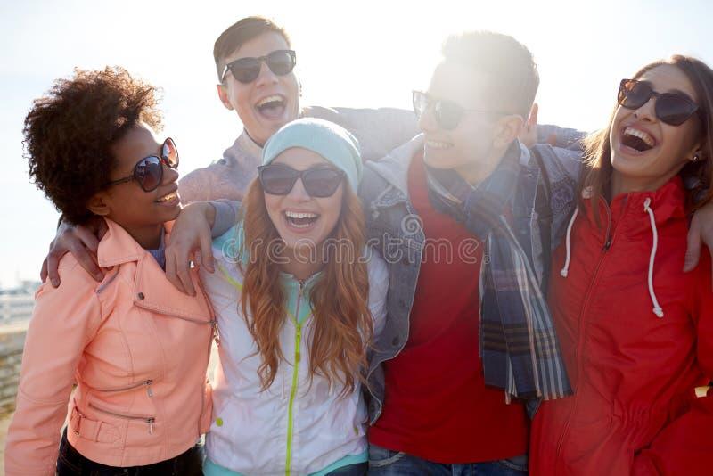 Uśmiechnięci przyjaciele śmia się na ulicie w okularach przeciwsłonecznych zdjęcie royalty free
