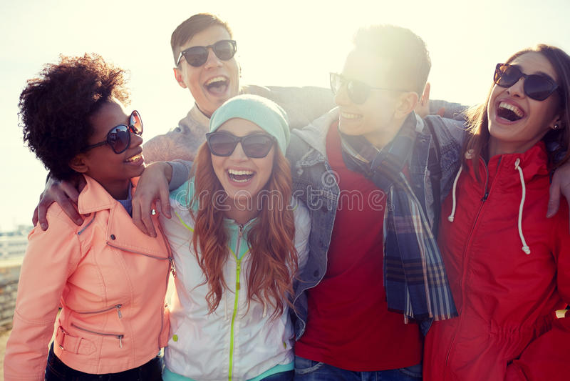 Uśmiechnięci przyjaciele śmia się na ulicie w okularach przeciwsłonecznych obraz stock