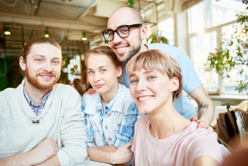 Uśmiechnięci przyjaciele bierze selfie w kawiarni fotografia royalty free