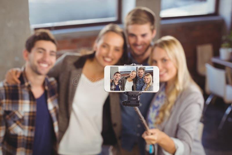 Uśmiechnięci przyjaciele bierze selfies z selfiestick zdjęcie stock
