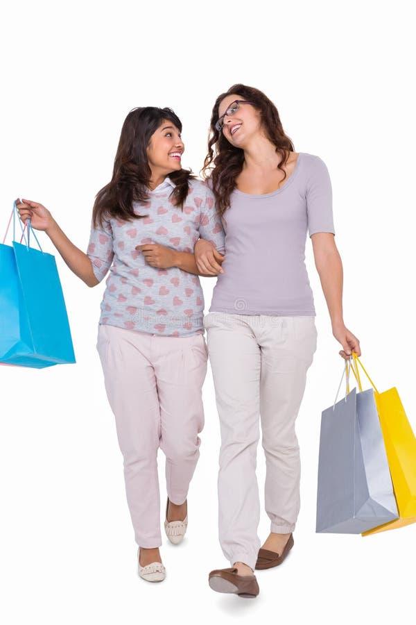 Uśmiechnięci przyjaciele chodzi z torba na zakupy zdjęcie royalty free