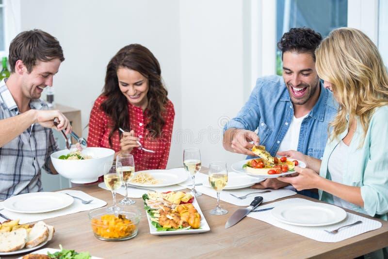 Uśmiechnięci przyjaciele ma jedzenie obrazy stock