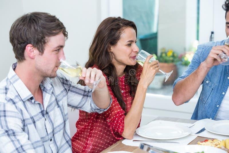 Uśmiechnięci przyjaciele pije białego wino obraz stock