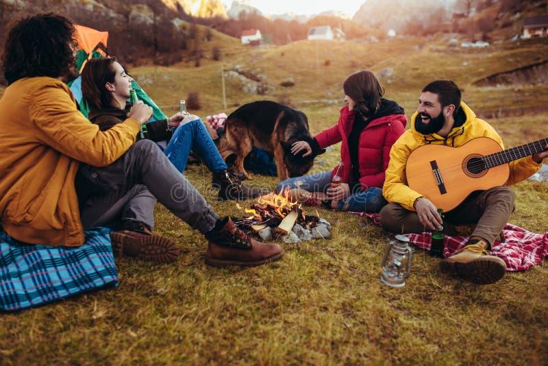 Uśmiechnięci przyjaciele siedzi wokoło ogniska w campingu zdjęcia stock