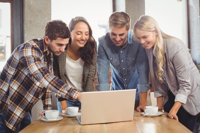 Uśmiechnięci przyjaciele stoi i wskazuje na laptopu ekranie zdjęcia stock
