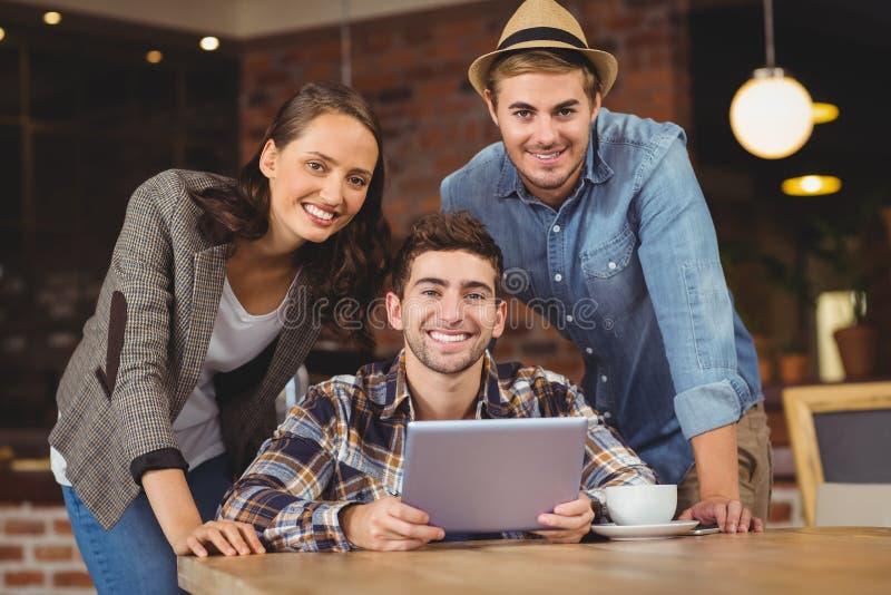 Uśmiechnięci przyjaciele używa pastylka komputer obraz royalty free