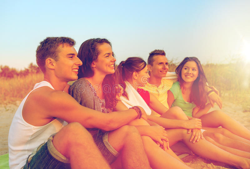 Uśmiechnięci przyjaciele w okularach przeciwsłonecznych na lato plaży zdjęcie stock