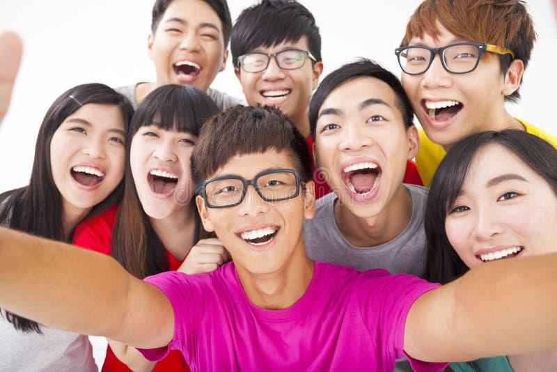 Uśmiechnięci przyjaciele z kamerą bierze jaźni fotografię zdjęcia stock