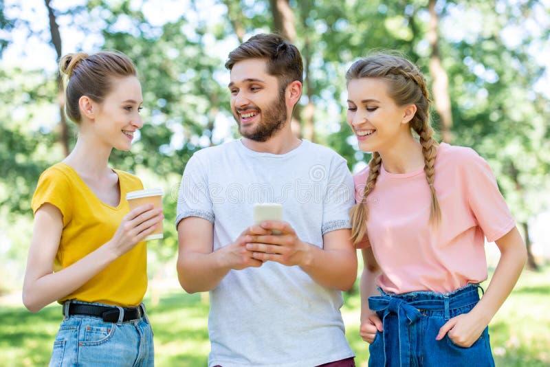 uśmiechnięci przyjaciele z kawą iść używać smartphone wpólnie fotografia royalty free