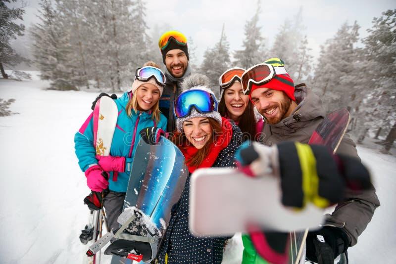 Uśmiechnięci przyjaciele z nartą na zima wakacjach - narciarki ma zabawę fotografia stock