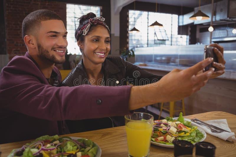 Uśmiechnięci przyjaciele z sałatkowymi talerzami bierze selfie w kawiarni zdjęcie stock
