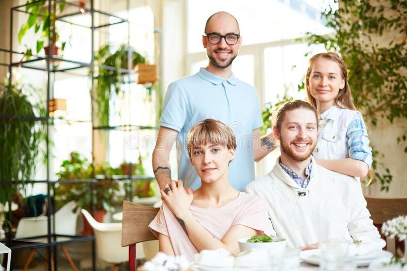 Uśmiechnięci przyjaciele zbiera w kawiarni zdjęcie royalty free