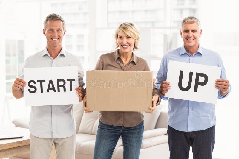Uśmiechnięci przypadkowi ludzie biznesu trzymać zaczynają up znaka obraz stock