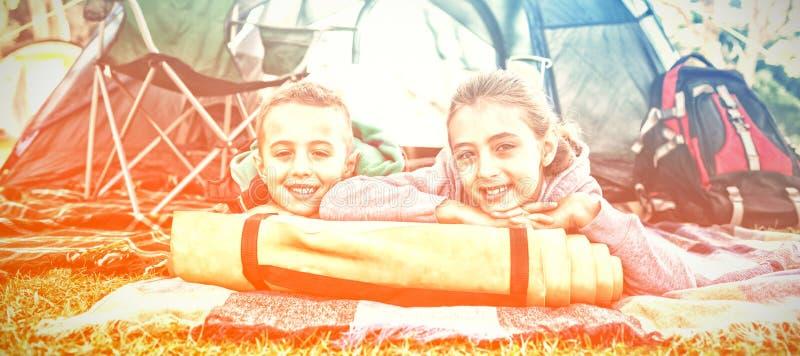 Uśmiechnięci rodzeństwa kłama na zewnątrz namiotu fotografia royalty free