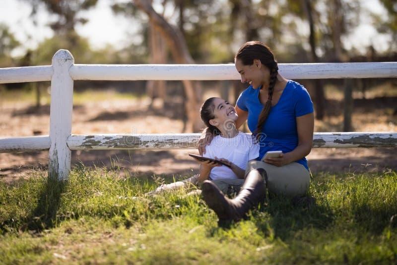 Uśmiechnięci rodzeństwa opowiada podczas gdy trzymający technologię zdjęcia stock