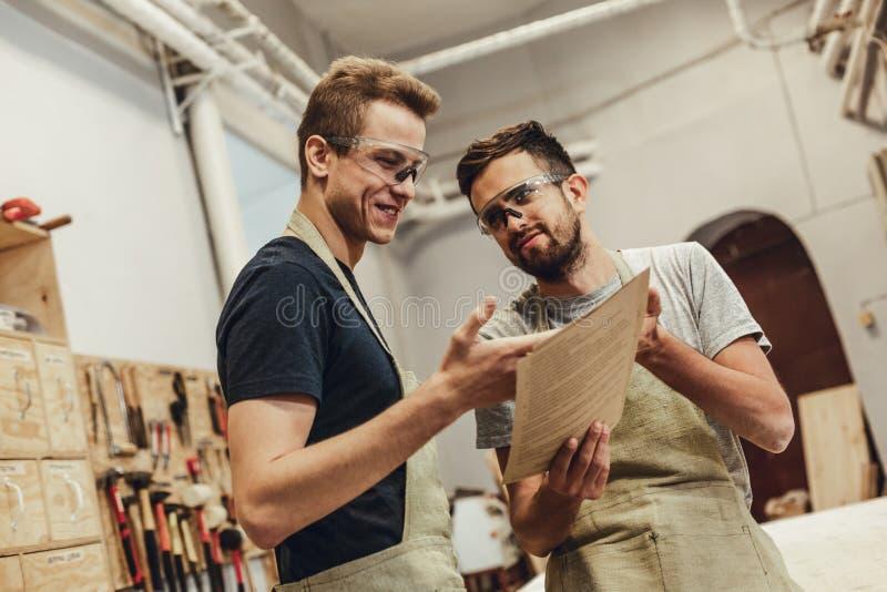 Uśmiechnięci rzemieślnicy wskazuje przy dokumentami fotografia stock