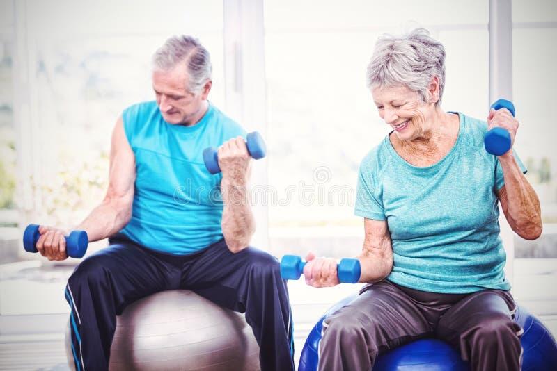 Uśmiechnięci starsi pary mienia dumbbells podczas gdy ćwiczący zdjęcie stock