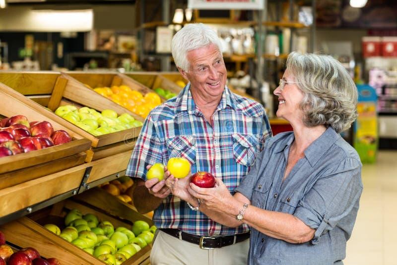 Uśmiechnięci starsi pary mienia jabłka zdjęcia stock