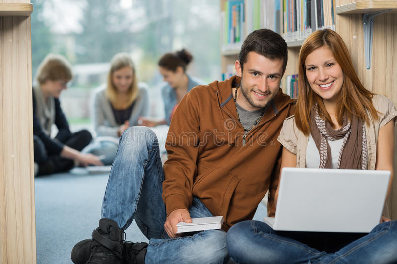 Uśmiechnięci studenci collegu z laptopem w bibliotece zdjęcie stock