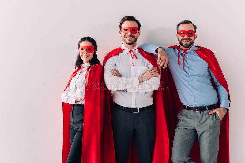 uśmiechnięci super biznesmeni patrzeje kamerę w maskach i przylądki obraz royalty free