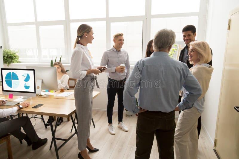 Uśmiechnięci szczęśliwi młodzi i starsi urzędnicy opowiada w coworki obraz royalty free