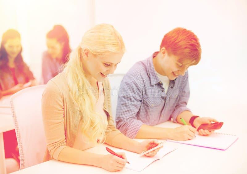Uśmiechnięci ucznie z notatnikami przy szkołą obrazy stock