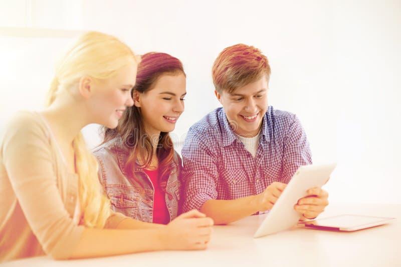Uśmiechnięci ucznie z pastylka komputeru osobistego komputerem przy szkołą fotografia stock