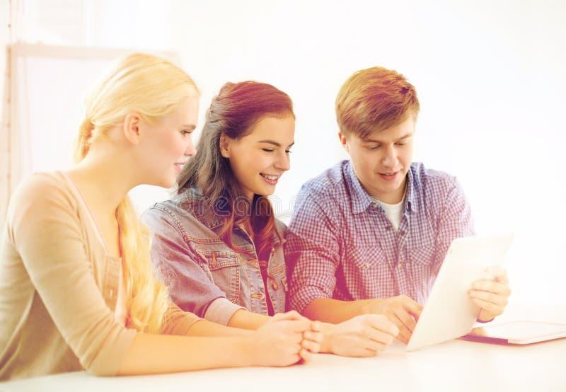 Uśmiechnięci ucznie z pastylka komputeru osobistego komputerem przy szkołą obraz royalty free
