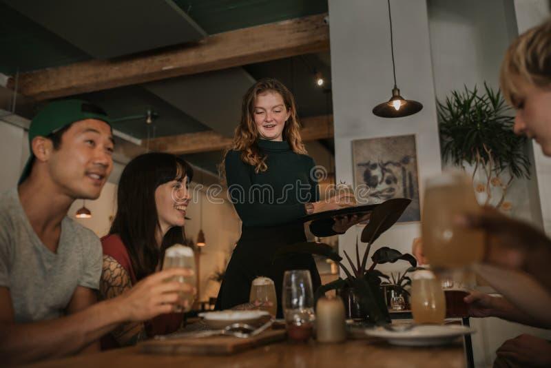 Uśmiechnięci watiress przynosi klientów piją w barze fotografia royalty free