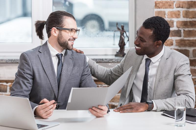 uśmiechnięci wielokulturowi partnery biznesowi siedzi przy stołowym patrzejący each inny zdjęcie stock