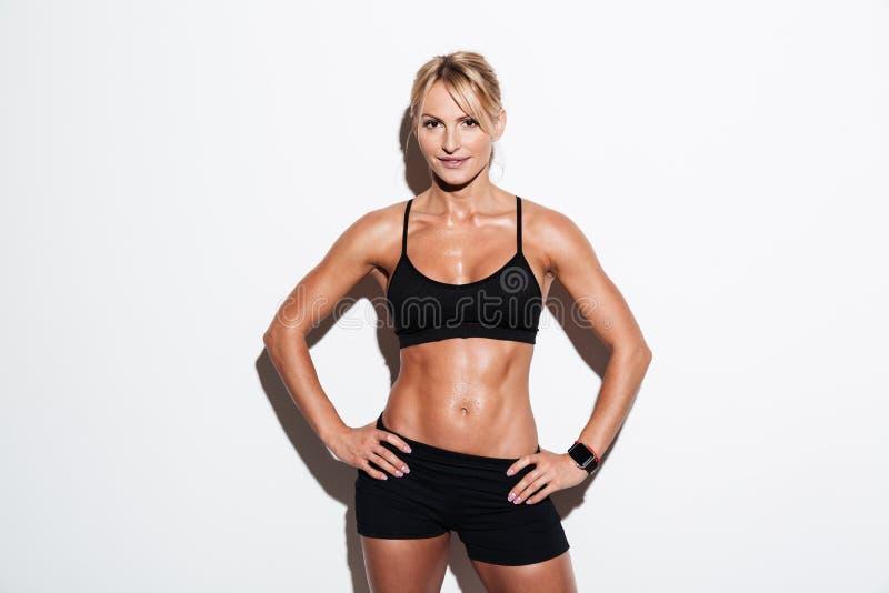 Uśmiechnięta ładna atlety kobieta pozuje podczas gdy stojący zdjęcia stock