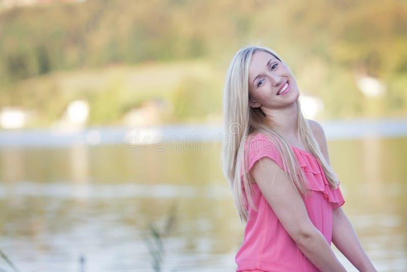 Uśmiechnięta Ładna Blond młoda kobieta przy brzeg jeziora obraz stock